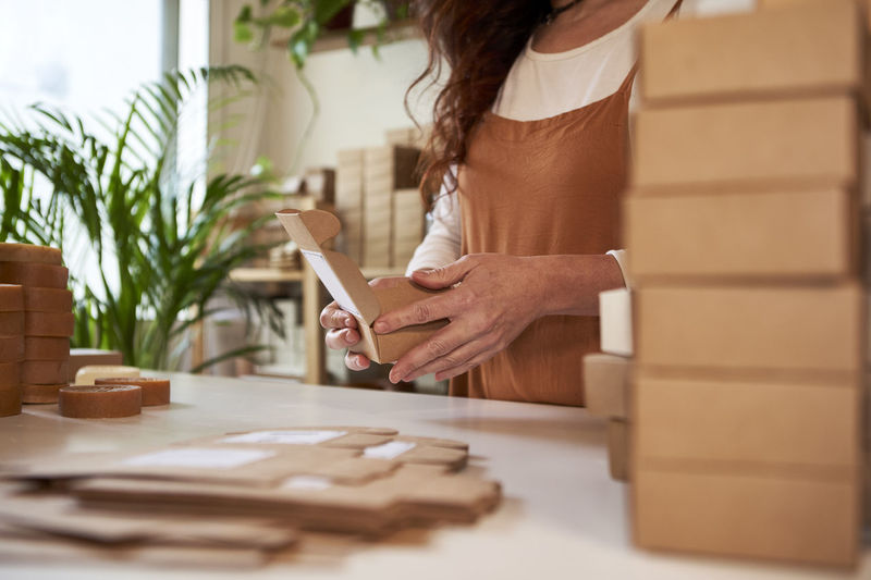 Midsection of woman holding smart phone at home