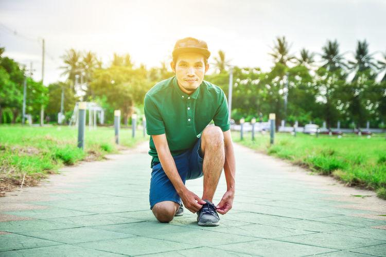 Portrait of man tying shoelace on footpath