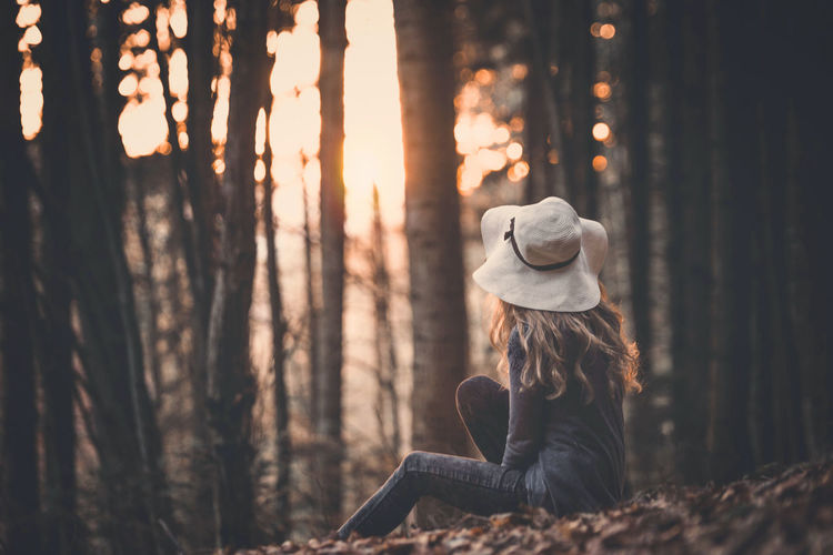 Woman In Hat Sitting On Field Against Trees During Sunset