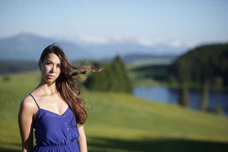 Portrait of beautiful young woman standing on field