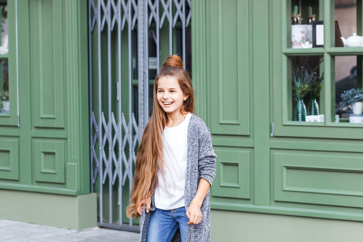 A beautiful young model in casual clothing in the street in front of the french caffe Architecture Building Exterior Casual Clothing Day Happiness One Person Outdoors Portrait Smiling