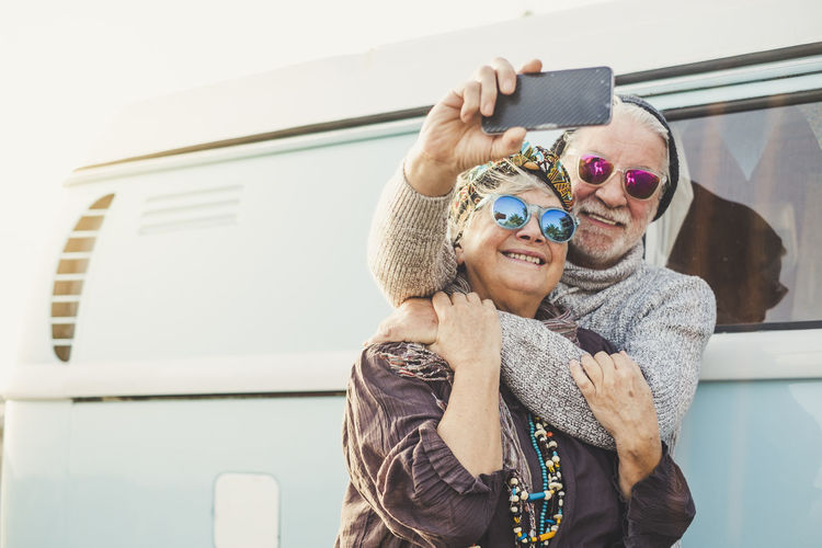 70 years old cheerful happy adult couple take a selfie picture outside a intage blue van with modern technologyh - tourism and tourist concept for people love travel together in relationship forever - retired happiness Elderly Couple Traveler Vanlife Retirement Enjoying Life Hippie Cold Temperature Caucasian Casual Clothing Grandparents Mother Father Scarf Emotion Positive Vibes 65-69 Years Wireless Technology Smiling Technology Women Smart Phone Selfie Happiness Portrait Photography Themes Real People Photographing Mobile Phone Camera Lifestyles Glasses Communication Portable Information Device Adult Fashion Outdoors Bonding Hugging Tourist Two People Relationship Gray Hair White Hair Old Senior Adult Choice Alternative Lifestyle