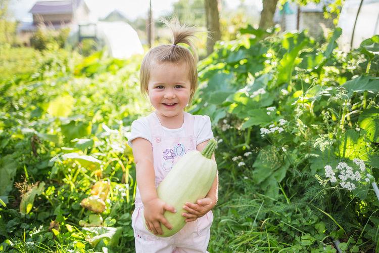 Portrait of smiling girl holding plants