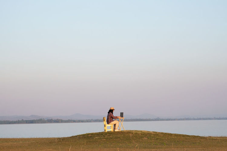 Woman using laptop over table sitting on grass by lake against clear sky