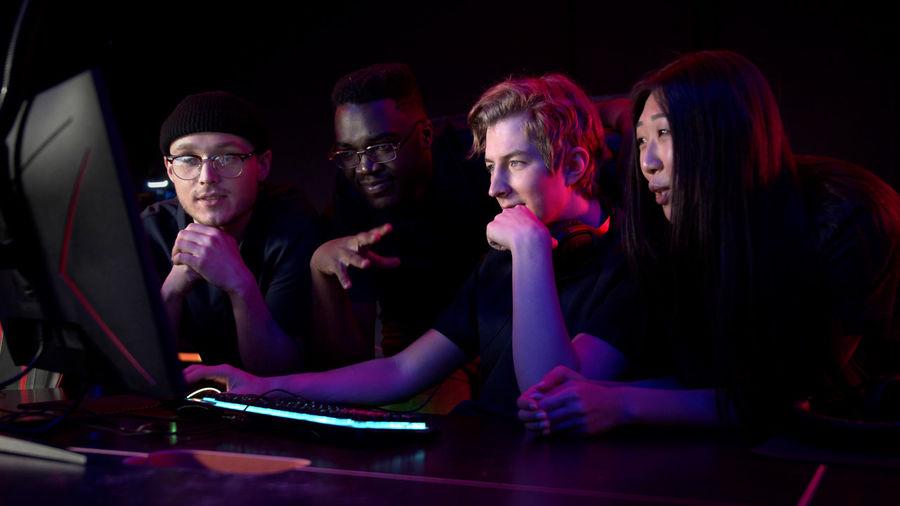 Man using computer by friends in darkroom