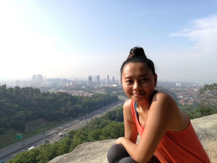 Portrait of smiling woman sitting on rock formation against city