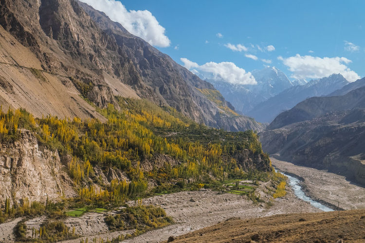 Landscape view of mountains and Hunza river in autumn. View from Karakoram highway, Gilgit Baltistan. Hunza valley, Pakistan. Pakistan Gilgit Baltistan Hunza Valley Environment Ecology Nature Landscape Mountains Karakoram Mountain Range Mountainscape Snow Capped Mountains Green Blue Travel Destinations Eco Tourism Stream Scenic Beautiful Scenery Outdoors Geology Landmark Rural Wilderness Area Into The Wild Trekking Hiking Adventure Ridge Natural Beauty Freshness Clean Air Fresh Air Pure Air Pollution Free Green City Green Pakistan Karakoram Highway Flowing River Countryside Journey Autumn Hills Scenics ASIA Vacations Trip View Backpacking Solotraveler Peaceful Peace And Quiet Mountainous Forest Poplar