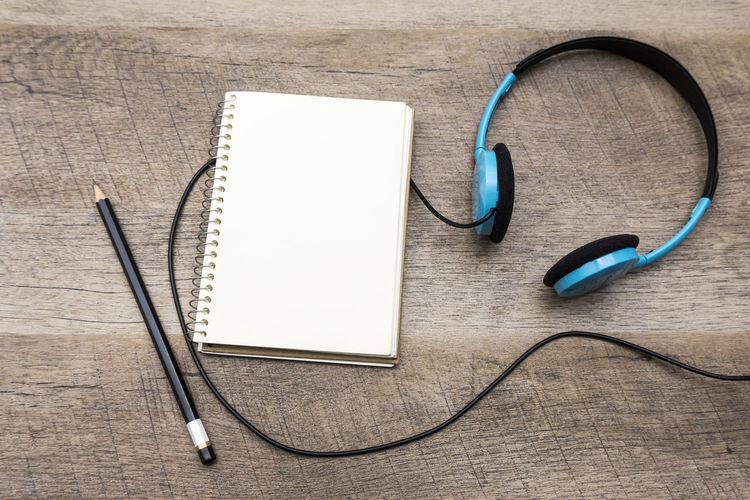 High angle view of headphones with book and pencil on table