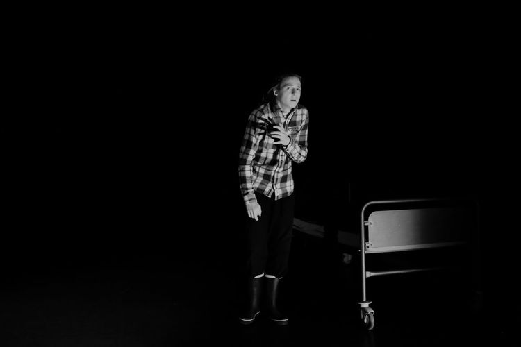 Full Length Of Teenage Boy Standing By Bed Against Black Background
