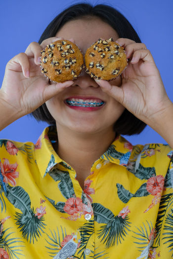 Close-up of woman with cakes against blue background