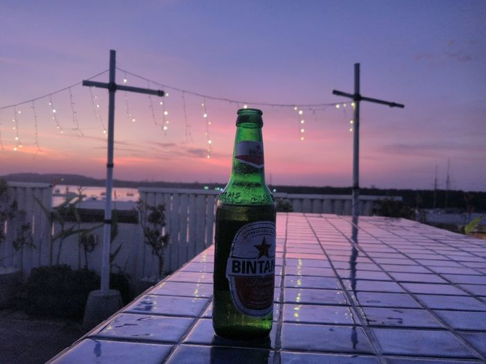 Don't judge anythink just from the cover. #Greenbottle #greenandpurple #sunset #coldestbeer #bintang #hangout #lonely #green #bottle Purple Alone Time Sunset_collection Beer Bintang Beer City Water Sunset Cityscape Sky Iris - Plant Lavender Cold Temperature Cold