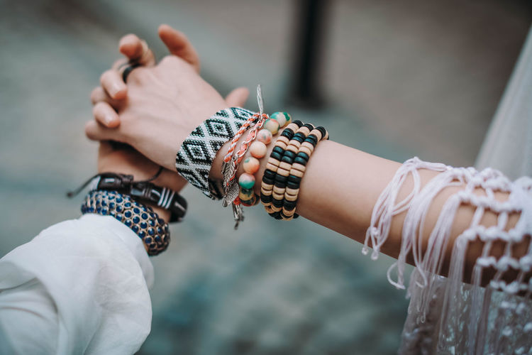 Female hands with bohemian accessories bracelets made of colored beads