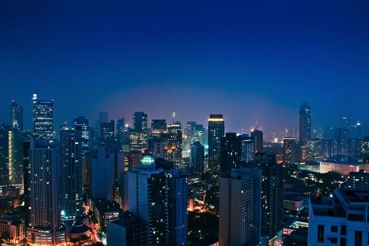 Illuminated cityscape against clear blue sky at night