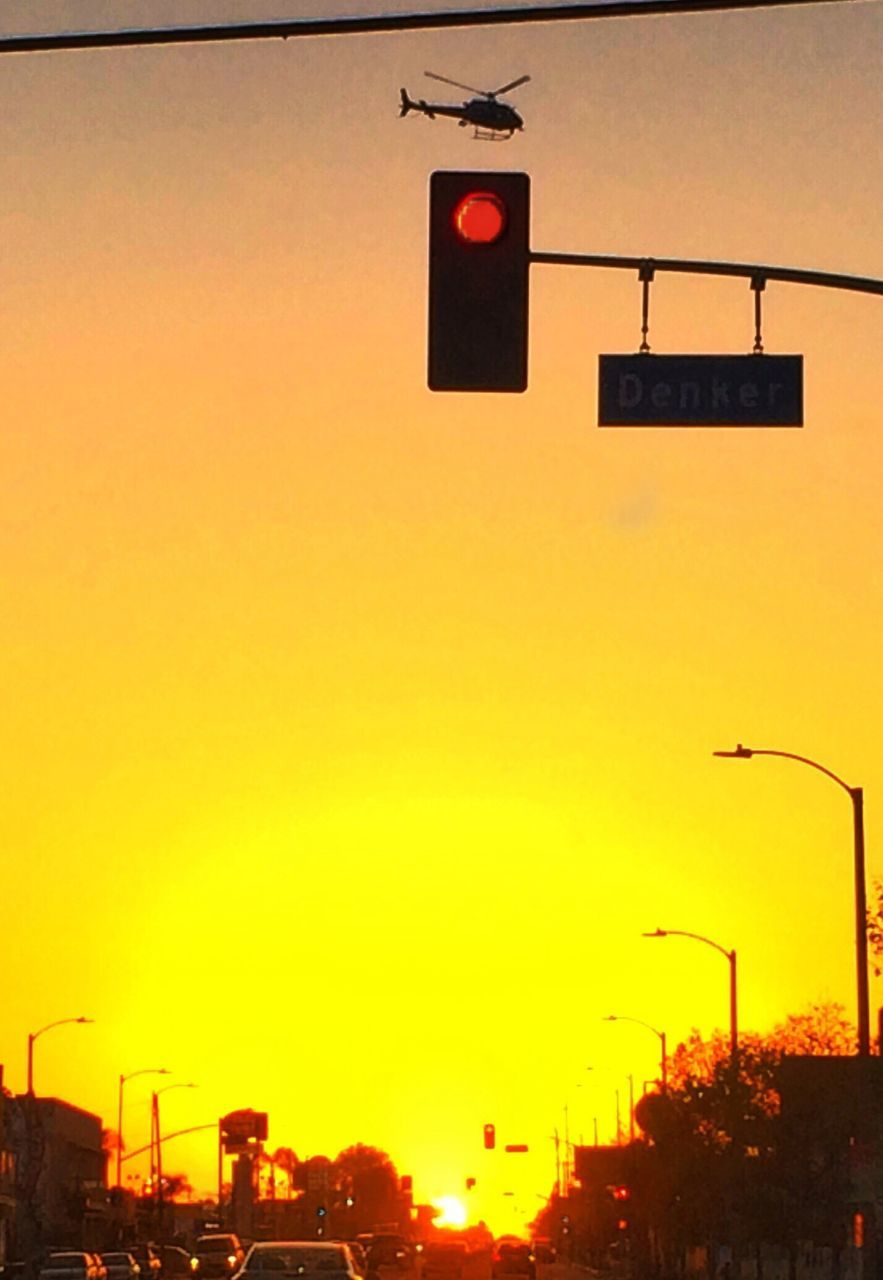 sunset, orange color, red light, outdoors, illuminated, low angle view, stoplight, communication, guidance, building exterior, no people, city, sky, architecture, clear sky, day
