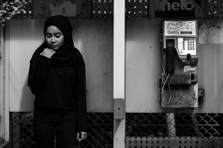 Thoughtful young woman standing by pay phone