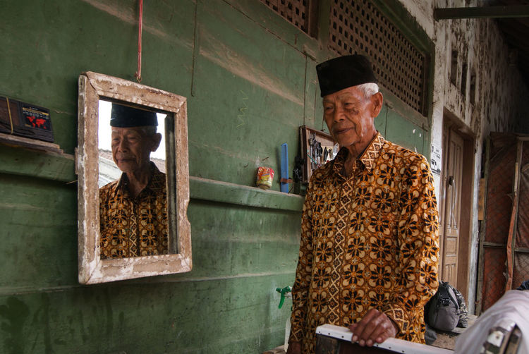 Man with reflection in mirror standing at home