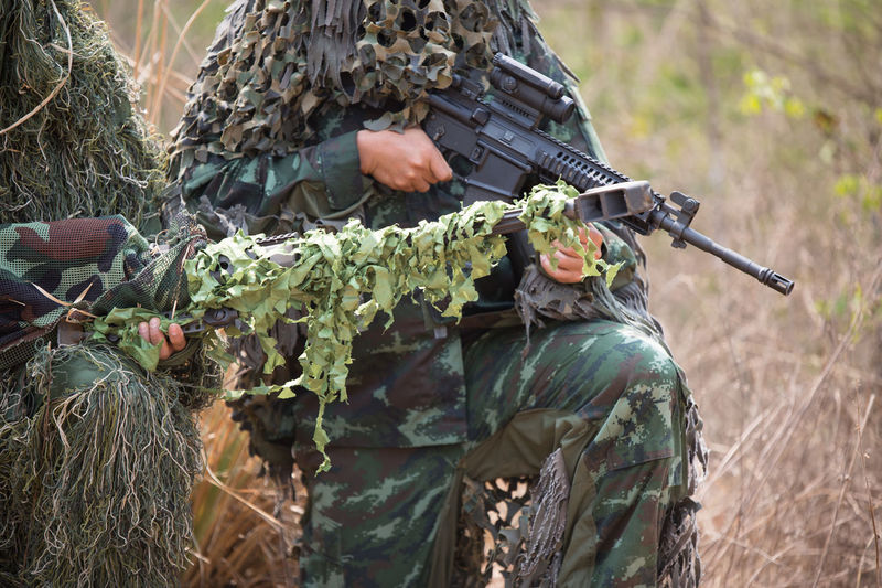 Army soldiers with rifle kneeling in forest