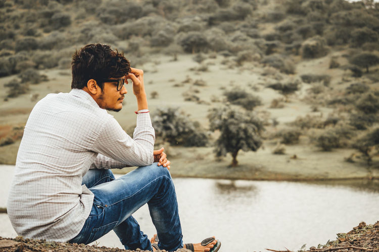Side view of young man sitting by lake