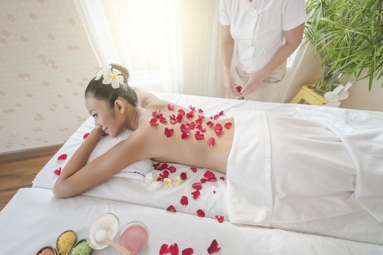 Shirtless Young Woman With Rose Petals Lying On Massage Table At Spa