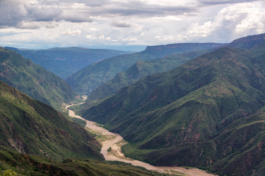 View of the rugged landscape of Chicamocha Canyon with Chicamocha River flowing below near Bucaramanga, Colombia Beauty In Nature Bucaramanga Canyon Chicamocha Chicamocha Canyon Cloud Cloud - Sky Colombia Day Landmark Landscape Mountain Mountain Range National Park Nature Outdoors Panachi Park River Santander Scenics Tranquil Scene Tranquility Tree Trees