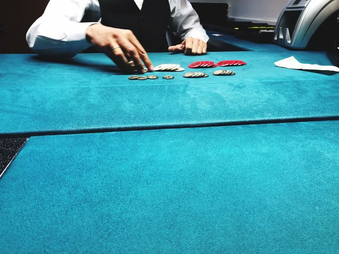 Midsection on man playing poker on table