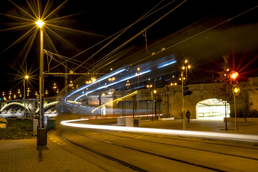 Night view of a tram stop. The lights of a tram lamps at night, image taken with a slow shutter speed. Image Lights Mobility In Mega Cities Red Tram View Architecture Blue Bridge - Man Made Structure Building Exterior Built Structure City Illuminated Lamps Long Exposure Motion Night Outdoors Public Transportation Slow Shutter Speed Speed Stop Street Light Transportation Tunnel