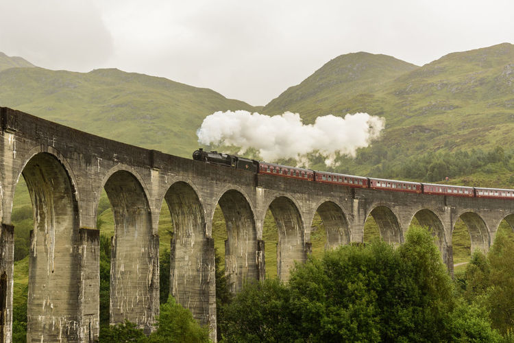 View Of Steam Train On Bridge Against Mountain