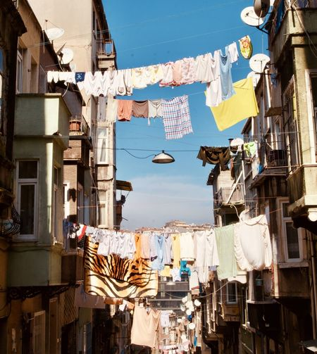 Low angle view of clothes hanging on buildings in city