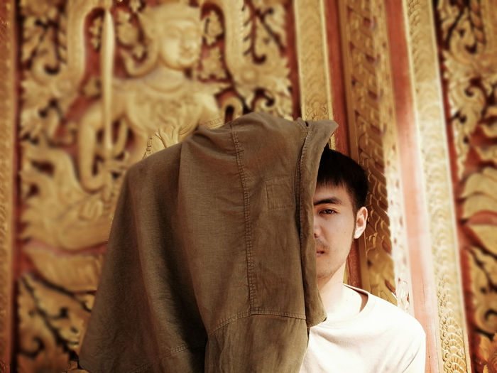 Portrait of man covering face with cloth