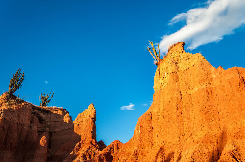 Low angle view of rock formations at tatacoa desert against blue sky