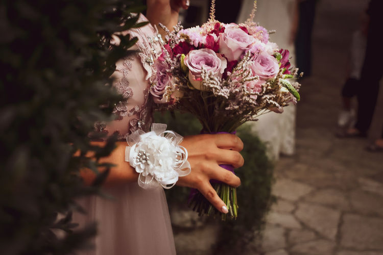 Midsection of bridesmaid holding flower bouquet