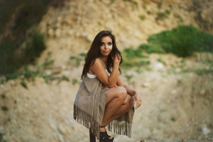Portrait of beautiful female model crouching against mountain