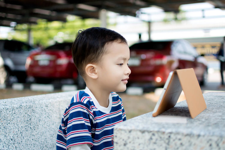 Close-Up Of Boy Looking At Digital Tablet On Table