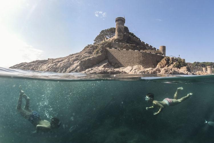 Full length of boys diving in sea