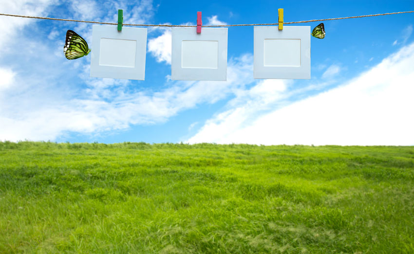 Low angle view of clothesline on field against sky