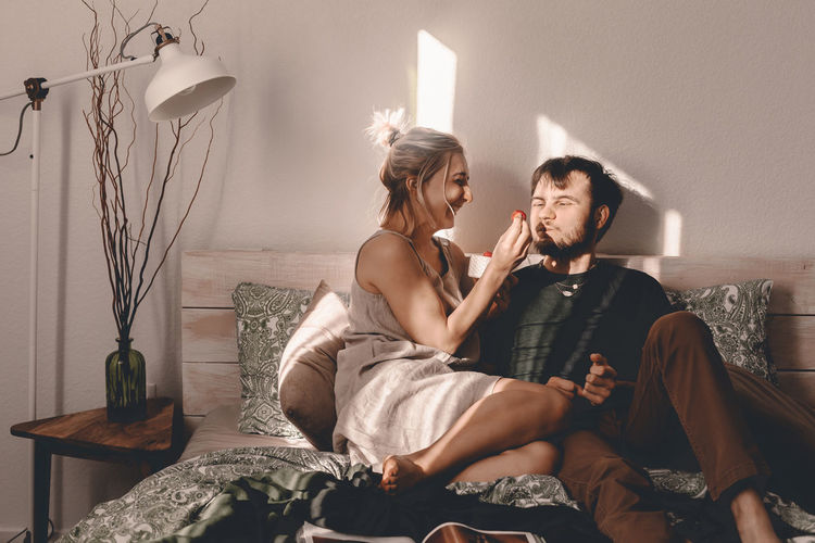 Woman feeding strawberry to man sitting on bed at home
