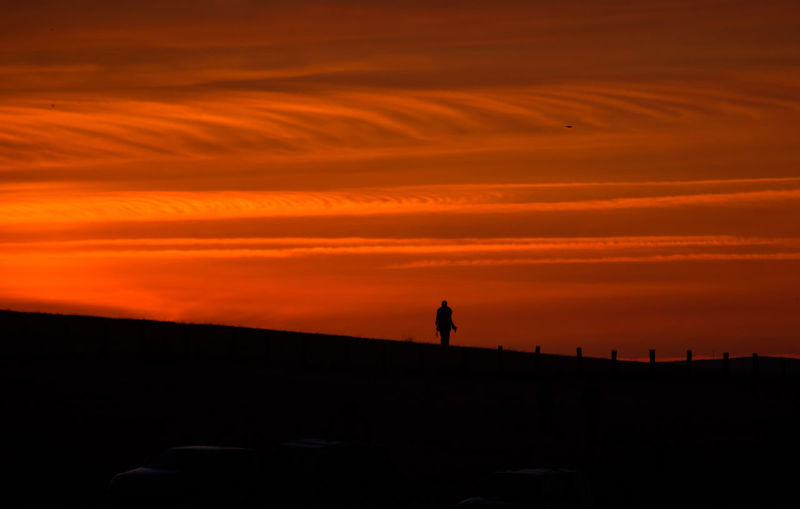 Silhouette person standing on field against orange sky