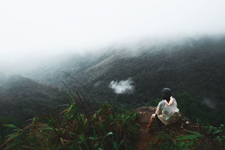 Rear View Of Person Sitting On Mountain Against Foggy Weather