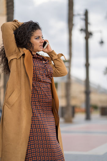 Woman talking on phone while standing at walkway