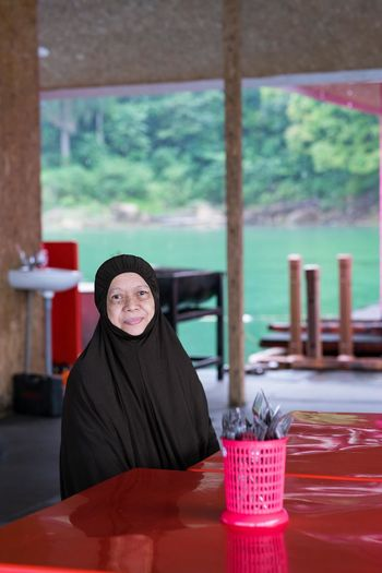 Portrait of woman wearing hijab sitting by table in restaurant