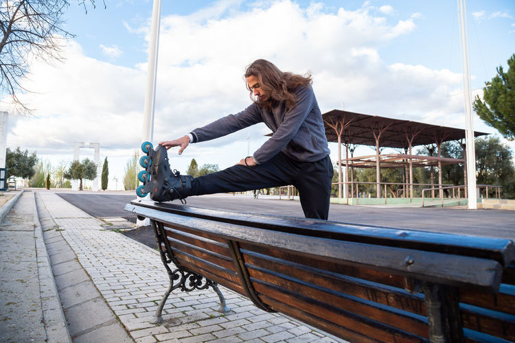 Side view of woman sitting on bench against sky