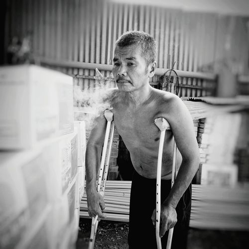 Shirtless disabled man exhaling smoke while standing with crutches
