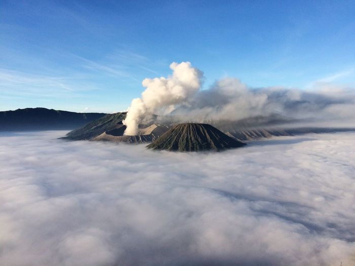Scenic View Of Mt Bromo Amidst Clouds Against Blue Sky
