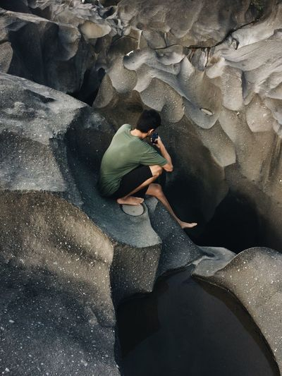 High angle view of man using mobile phone while sitting on rock