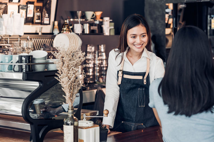 Smiling owner talking to customer while standing at counter in cafe