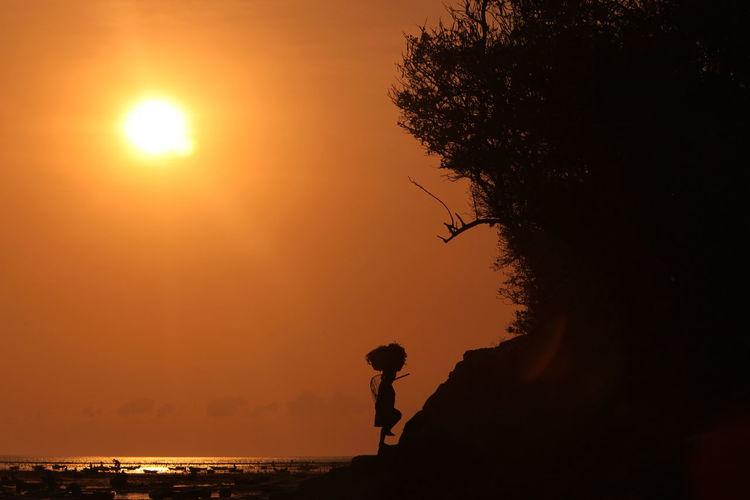 Silhouette worker carrying basket walking on rock against orange sky at shore