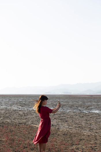 Side view of woman photographing while standing against sky