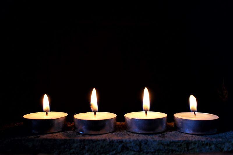 Close-Up Of Candles Burning At Night