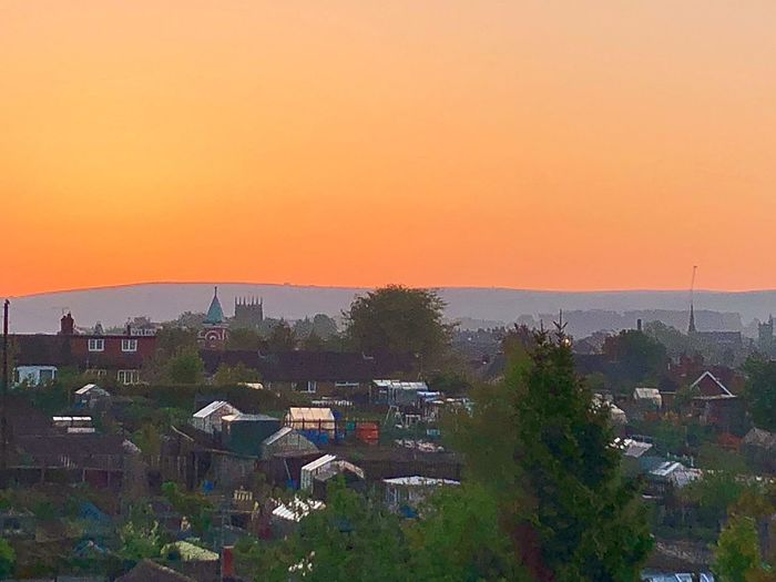 High angle view of townscape against orange sky