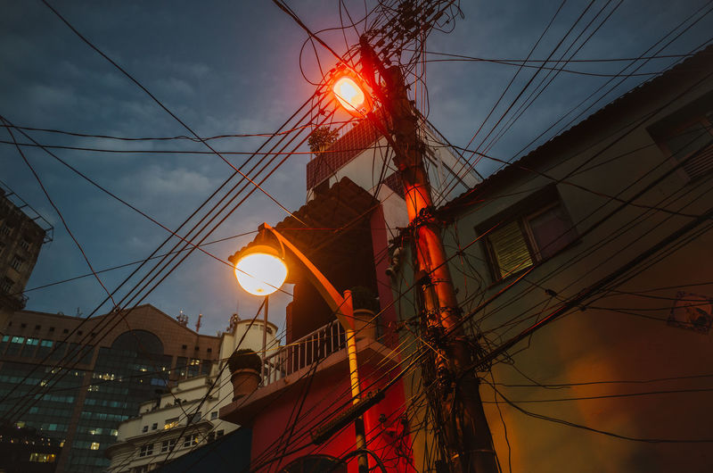 Street lamps and cable in Rio de Janeiro, Brazil Night City Electricity Pylon Sunset Illuminated Technology Electricity  Cable Fuel And Power Generation Power Line  Power Supply Power Cable Street Light Lamp Post Electric Light Electrical Grid